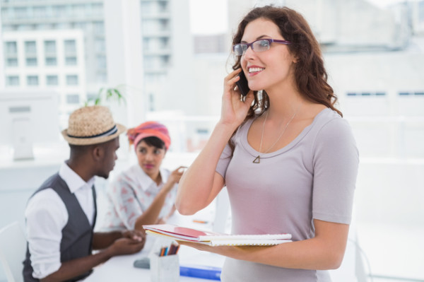 Smiling businesswoman phoning and holding notepad in the office